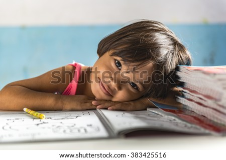 a very young girl student in the school has her head on the exercise book and smiling friendly. Thai school in a small village - stock photo