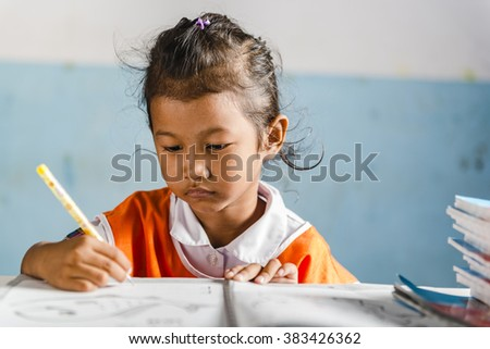 a very young girl student in the school make her exercises. Thai school in a small village