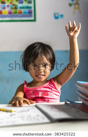 a very young student girl has a question for the teacher. Thai school in a small village - stock photo