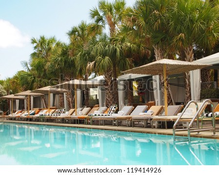 A vibrant blue swimming pool with reflections on the water surface is surrounded by palm trees and lounge chairs with wicker umbrellas.