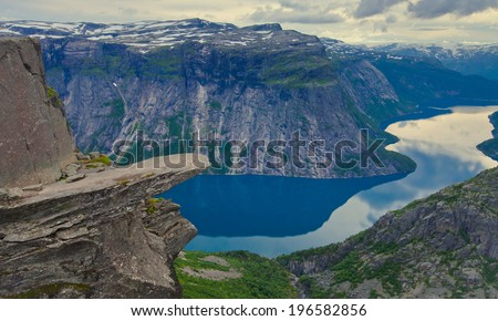 A vibrant picture of famous norwegian hiking place - trolltunga, the trolls tongue, rock skjegedall, with a tourist, and lake ringedalsvatnet and mountain panoramic scenery epic view, Norway  - stock photo