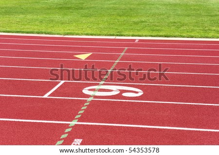 A vibrant track and field setting with striped lanes and healthy grass.