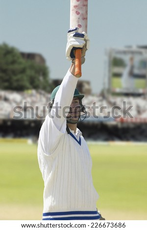 A victorious batsman holding his bat - stock photo