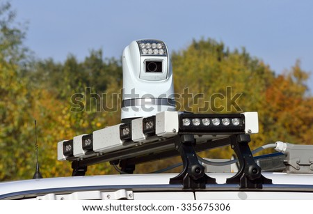 A video camera on the roof of a police car is watching and filming rioting people during a demonstration - stock photo