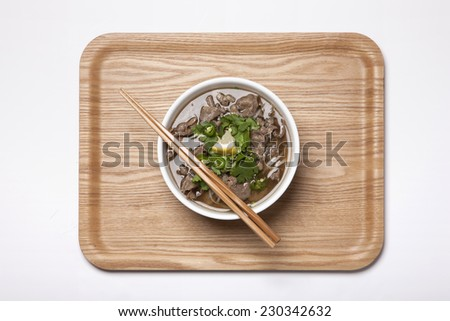 A Vietnam rice noodles with beef and wood chopsticks, wood tray isolated white, top view at the studio. - stock photo