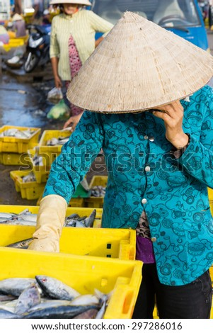 A Vietnamese woman is listening her phone in Long Hai Fish market, Ba Ria - Vung Tau, Vietnam
