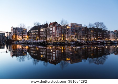 A view along the Oudeschans Canal in Amsterdam at twilight. Building, boats and reflections can be seen. There is space for text.
