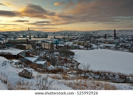 A view from top on Polyarny city in Russia: port, ships, houses and trees in winter. Sunset over hills