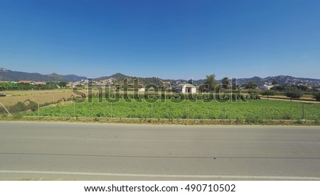 A view from train vindow of spanish crop fields, mountains, countryside. Smooth camera slide shot of green plants meadows, blue clear sky, and rare cars on the roads.