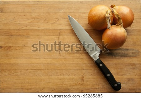 A view looking down on a group of onions and a large knife on a worn butcher block cutting board - stock photo