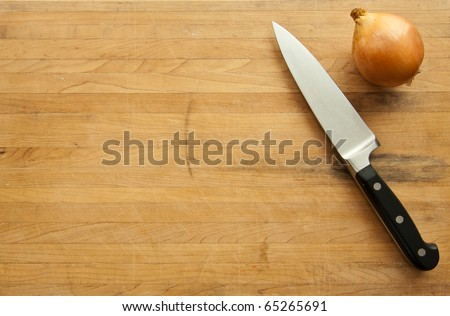 A view looking down on a large knife and onion on a worn butcher block cutting board. - stock photo