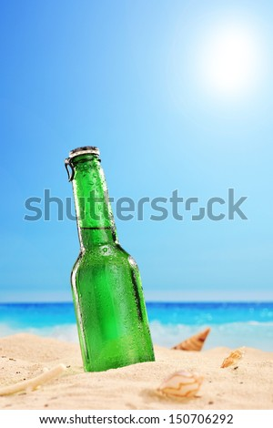 A view of a beer bottle on a sandy beach, with clear sky and sun, next to the sea  - stock photo