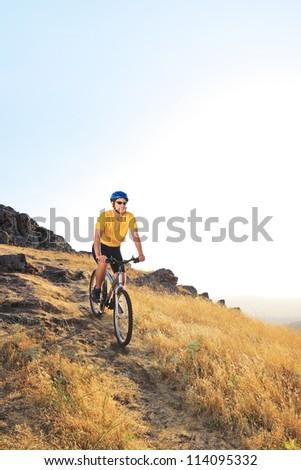 A view of a biker riding a mountain bike on a sunset, Macedonia - stock photo
