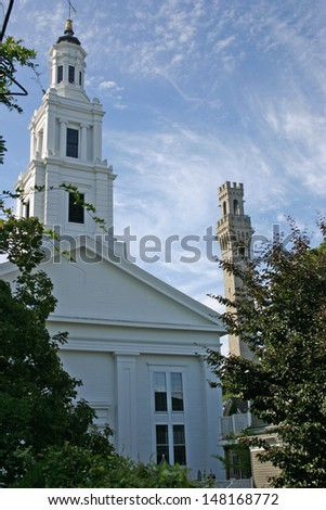 A view of a church and the Pilgrim Monument in Provincetown, Massachusetts - stock photo