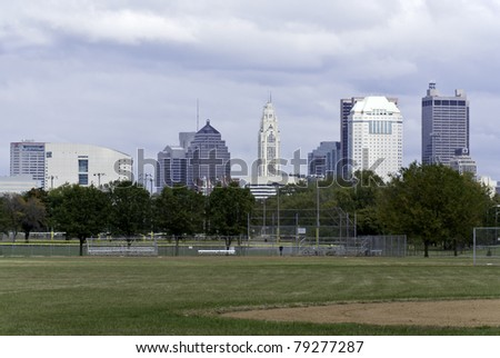 A view of a city scape as seen with a baseball field in the foreground and an overcast sky in the background.