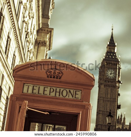 a view of a classic red telephone booth and the Big Ben in the background, in London, United Kingdom, with a filter effect - stock photo