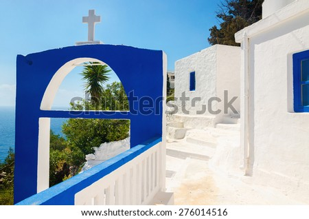 A view of a Greek church with iconic blue colors and see in the background on Greek island, Kalymnos, Greece - stock photo