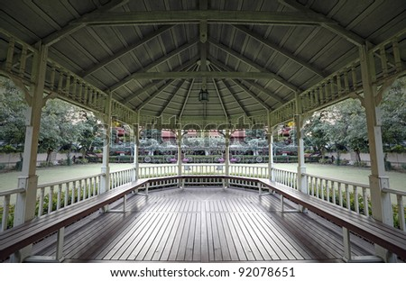 A view of a green garden from the interior of a vintage gazebo bandstand. - stock photo
