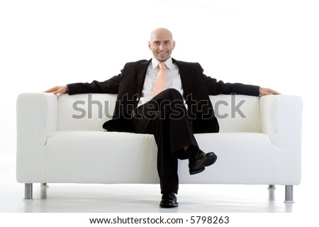 A view of a happy, satisfied businessman, relaxing on a large, white sofa.  Isolated on white background. - stock photo