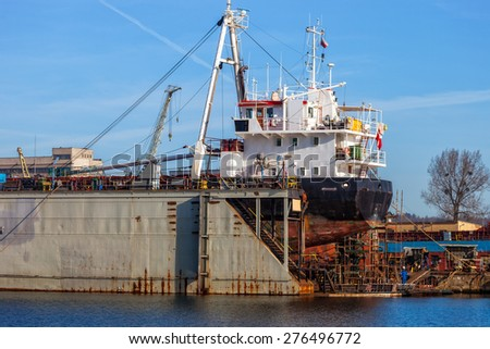 A view of a large ship under repair in dry dock at a shipyard.