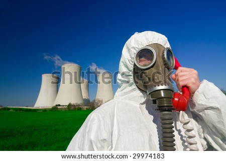 A view of a man wearing a breathing mask and a hazmat suit, standing in front of a nuclear power station and talking on a red phone. - stock photo