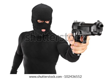 A view of a man with robbery mask holding a gun isolated against white background - stock photo