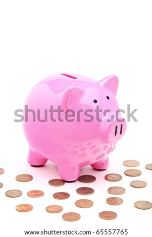A view of a pink piggy bank and many coins isolated on white background - stock photo