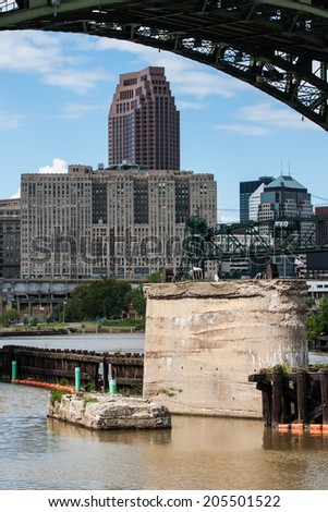 A view of a portion of downtown Cleveland, Ohio and the Cuyahoga River, framed by one of the arches of the Hope Memorial Bridge.  View is from the Scranton Flats Towpath recreation area. - stock photo