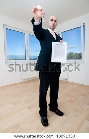 A view of a real estate agent in a new home, holding house keys and a contract. - stock photo