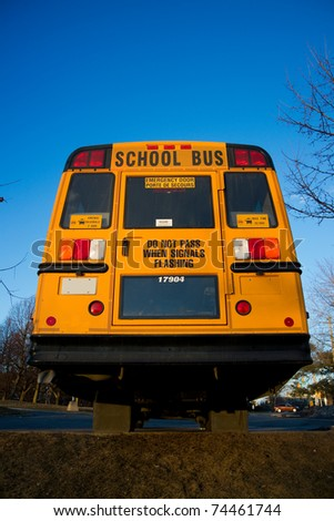 A view of a traditional yellow school bus from the rear. - stock photo