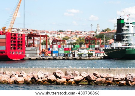 a view of a typical port, full of containers. crane and freight vessel waiting to be loaded or unloaded in Istanbul, Turkey. cityscape and clear sky behind the port. - stock photo