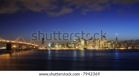 A view of Bay Bridge and San Francisco downtown decorated by Christmas lighting at dusk (shot from Treasure Island). Copyspace on top and bottom - stock photo