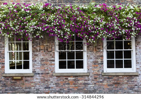 A view of beautiful hanging baskets over windows in an English Countryside Town. - stock photo