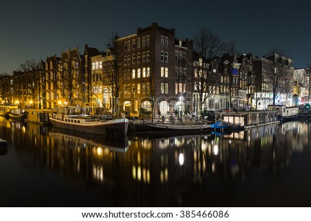 A view of buildings and boats along the Amsterdam Canals at night. Reflections can be seen in the water. There is space for copy space. - stock photo