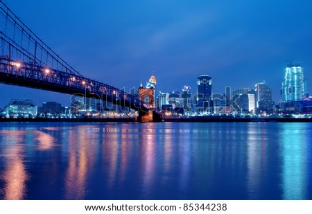 A view of Cincinnati, Ohio?s skyline cityscape overlooking the Ohio River at night. - stock photo