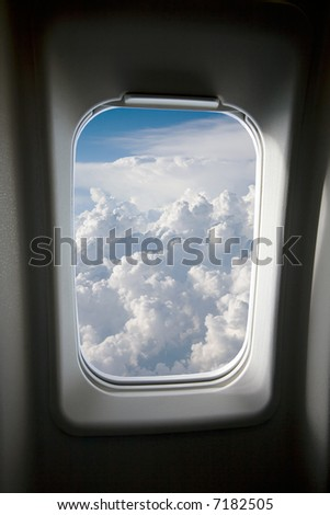 A view of clouds from an airplane window. - stock photo