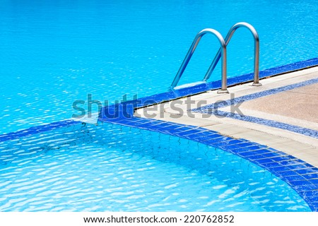 A view of curved light clear blue swimming pool with steel ladder, outdoor swimming pool. - stock photo
