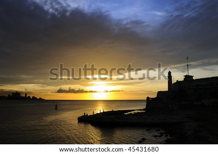 "A view of ""el morro"" fortress silhouette in Havana bay entrance at sunset - stock photo"
