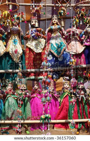 A view of ethnic decorative item consisting of colorful bead and elephants made of colorful cloth, on the backdrop of traditional Indian Rajasthani puppets. - stock photo