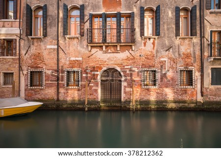 A view of old buildings along the Venetian Canals in the Cannaregio District of Venice. - stock photo