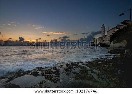 A view of old hispanic fortress El Morro in Havana bay entrance at sunset - stock photo