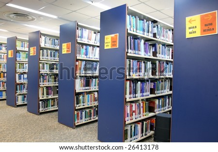 A view of rows of bookshelves and a study area inside a library - stock photo