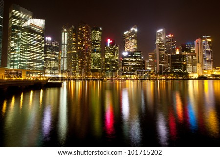 A view of Singapore business district in the night time with water reflections. - stock photo