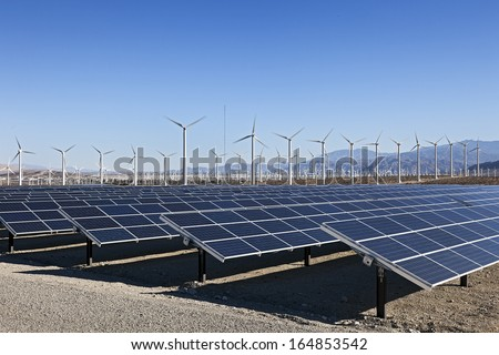 A View of Solar Panels and Wind Turbine in the Field - stock photo