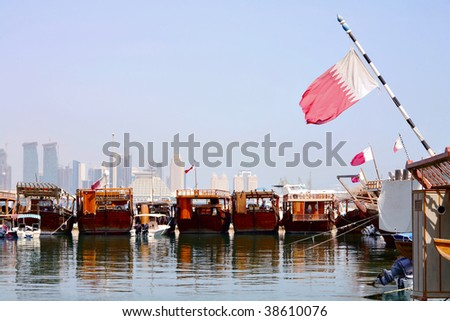 A view of the dhows in Doha harbour, with the Qatari flag flying from them and the new city skyline in the background. - stock photo