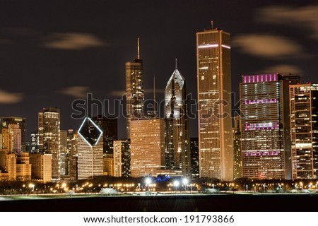 A view of the famous Chicago skyline at night on a cloudy day.
