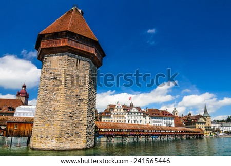 A view of the famous wooden Chapel Bridge of Luzerne, Lucerne in Switzerland, with the water tower and Reuss River. - stock photo