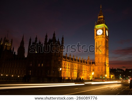 A view of the Houses of Parliament in London at Dusk. The blur of traffic can be seen going past. - stock photo