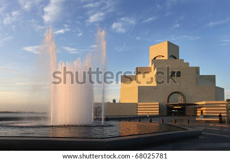 A view of the imposing Museum of Islamic Art in Doha, Qatar, Arabia under a cloudy winter sky, with the water catching the evening sun. - stock photo