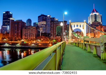 A view of the Pittsburgh, Pennsylvania cityscape at night from the Roberto Clemente Bridge overlooking the Allegheny River. - stock photo